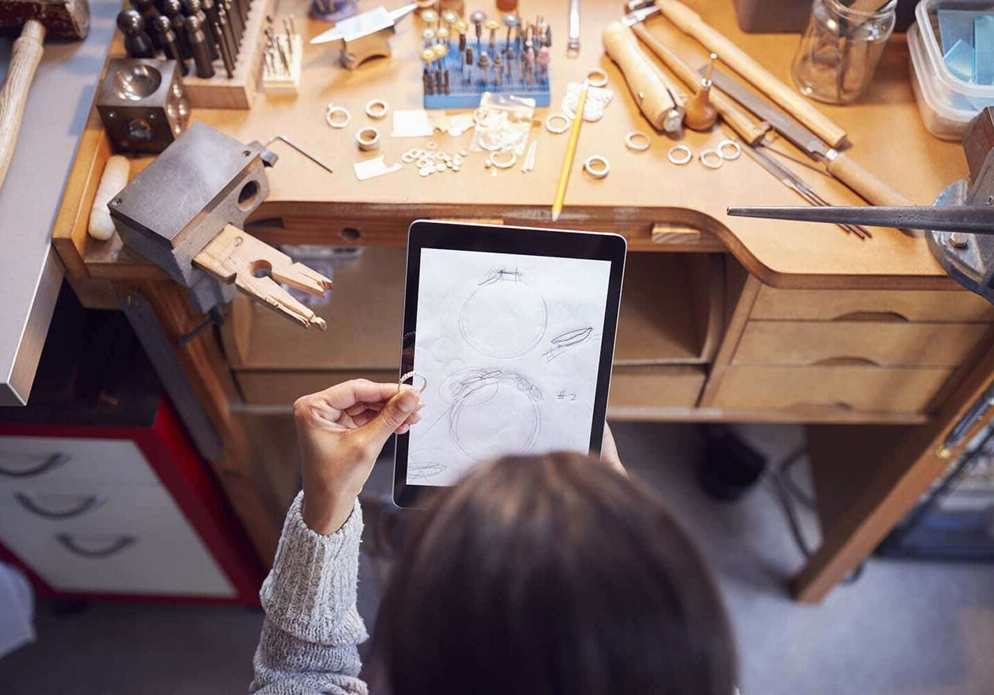 Overhead View Of Female Jeweller Comparing Ring With Drawn Design On Digital Tablet In Studio
